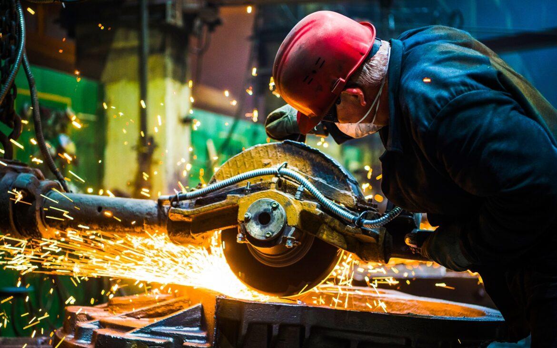 Worker grinding metal, metal grinding machine with sparks, metal sawing.